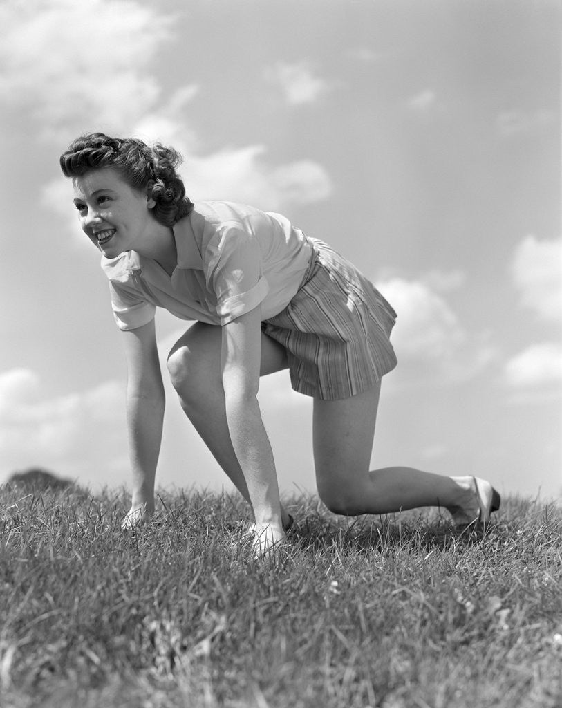 Detail of 1940s Young Teen Woman Kneeling In Grass In Track Race Ready Starting Position by Corbis