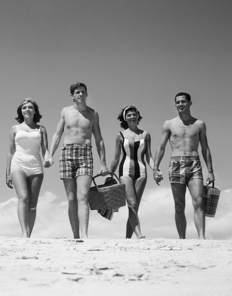 Detail of 1960s Teenage Couples Wearing Bathing Suits On Beach Carrying Picnic Baskets by Corbis