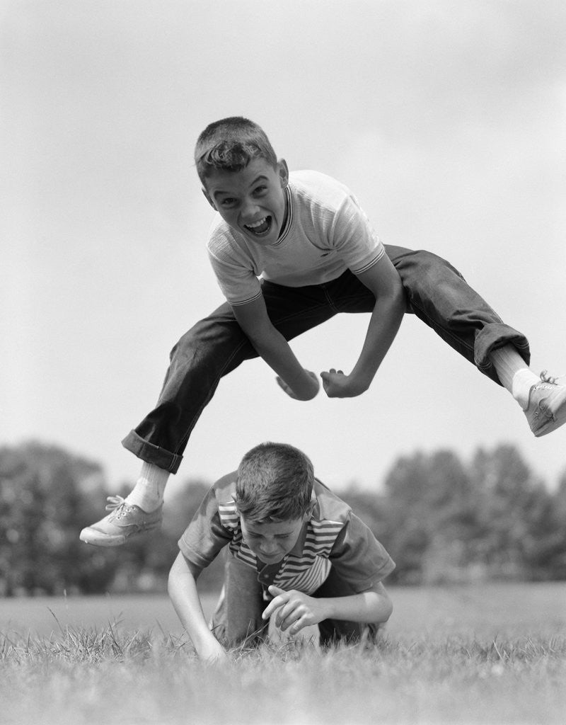 Detail of 1960s Retro Boys Playing Leap Frog Outside Sky Grass Jump Jumping Crouching by Corbis