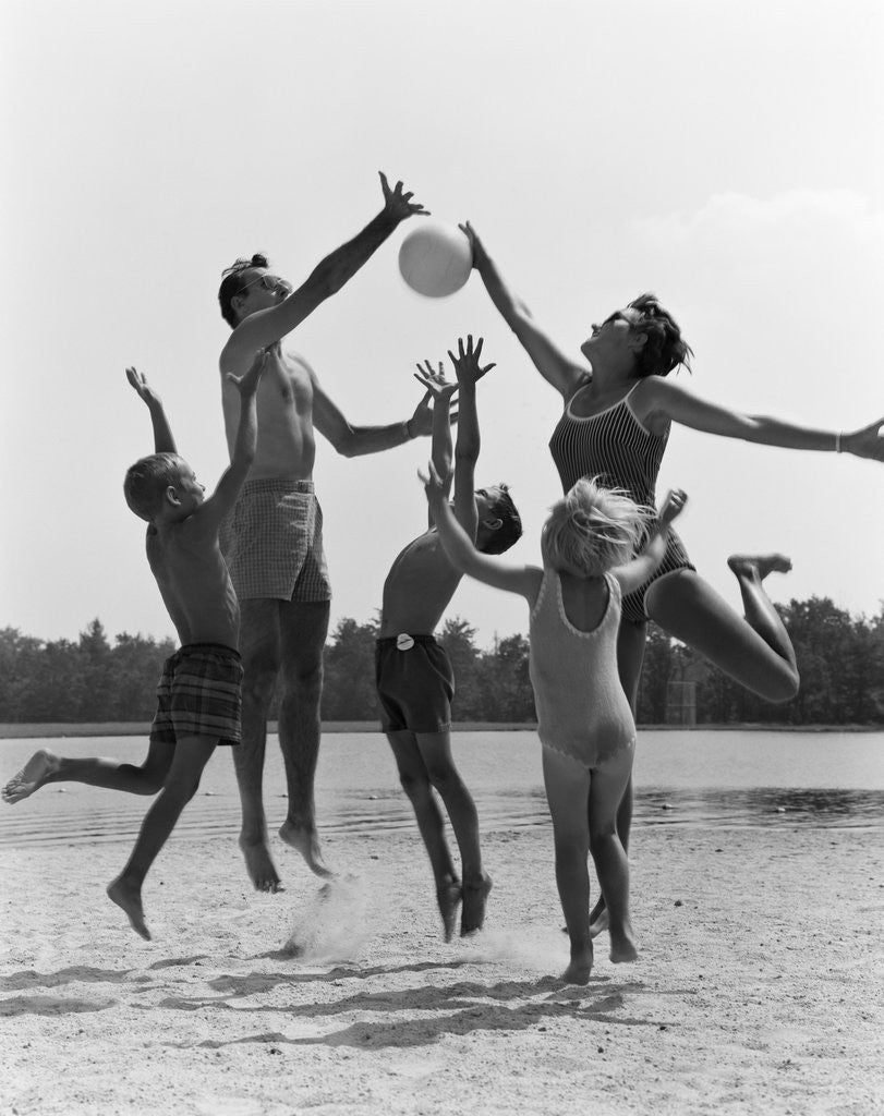 Detail of 1960s Family Jumping Playing Beach Volleyball by Corbis