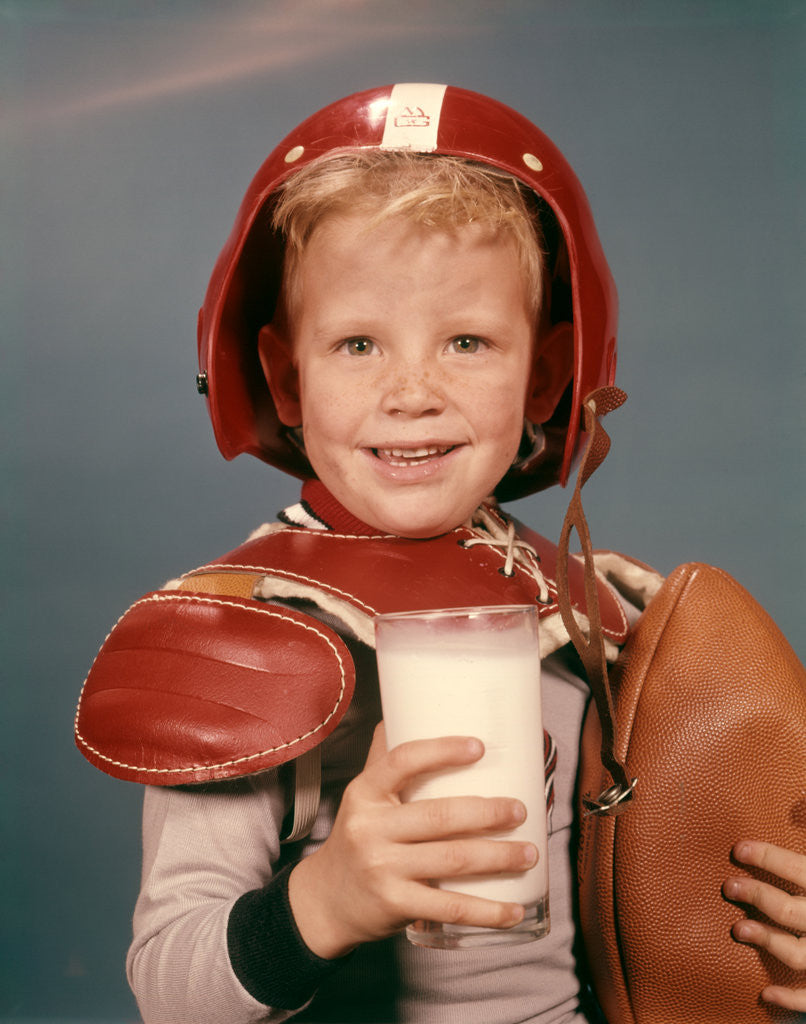 Detail of 1960s Boy Wearing Red Helmet Football Shoulder Pads Holding Glass Milk and Football by Corbis