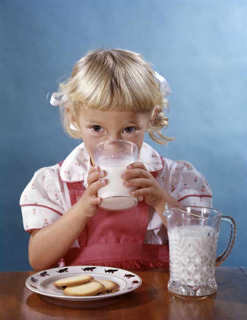 Detail of 1950s 1960s Girl Drinking Milk Plate Cookies by Corbis