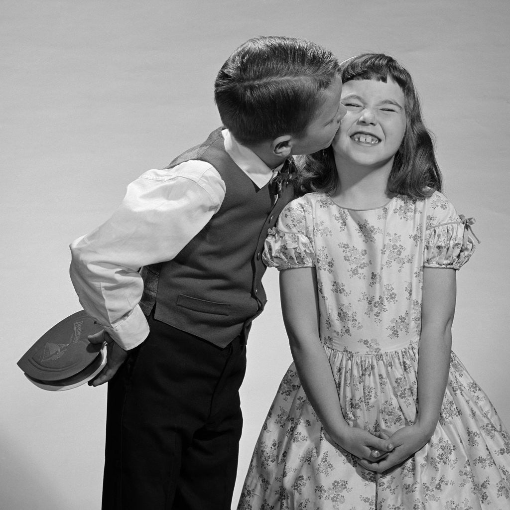 Detail of 1950s 1960s Boy In Vest and Bow Tie Holding Valentine Candy Kissing Cheek Of Girl Making A Face by Corbis