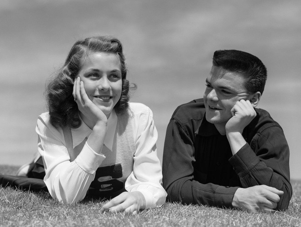Detail of 1950s Teenage Couple Laying On Grass, Boy Gazing At Girl Wearing Cheerleader Sweater by Corbis