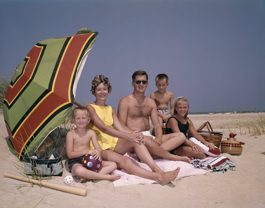 Detail of 1960s Family On Sunny Beach Under Umbrella With Picnic Basket by Corbis