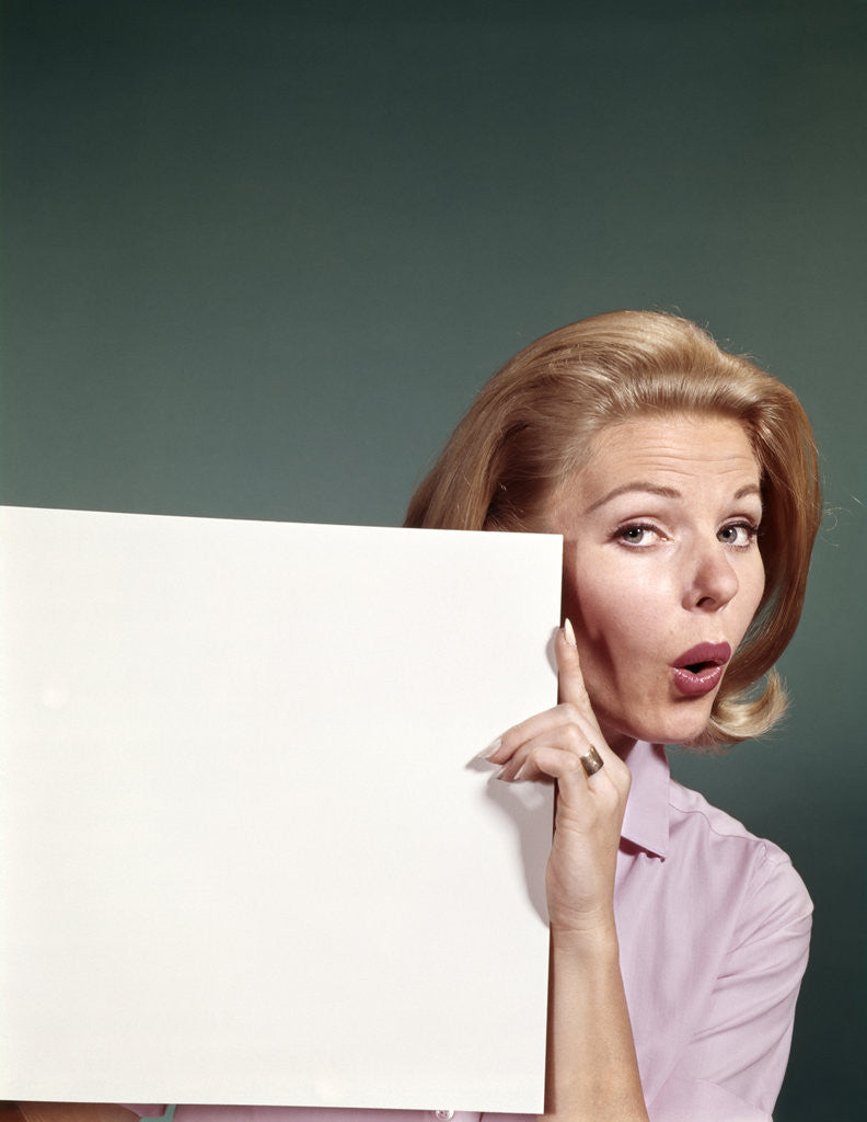Detail of 1960s Portrait Of Surprised Woman Peeking Around Sign Board by Corbis