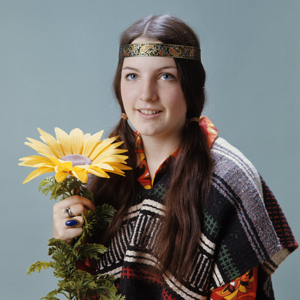 Detail of 1960s 1970s Teenage Girl With Pigtails Wearing Headband And Serape Holding Sunflower by Corbis