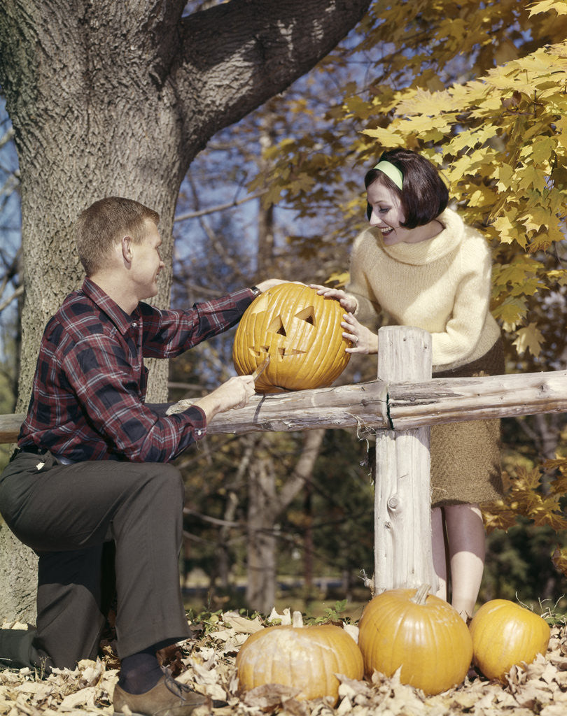 Detail of 1960s Young Couple Man Woman In Autumn Woods Carving Halloween Jack-O-Lantern Pumpkin by Corbis
