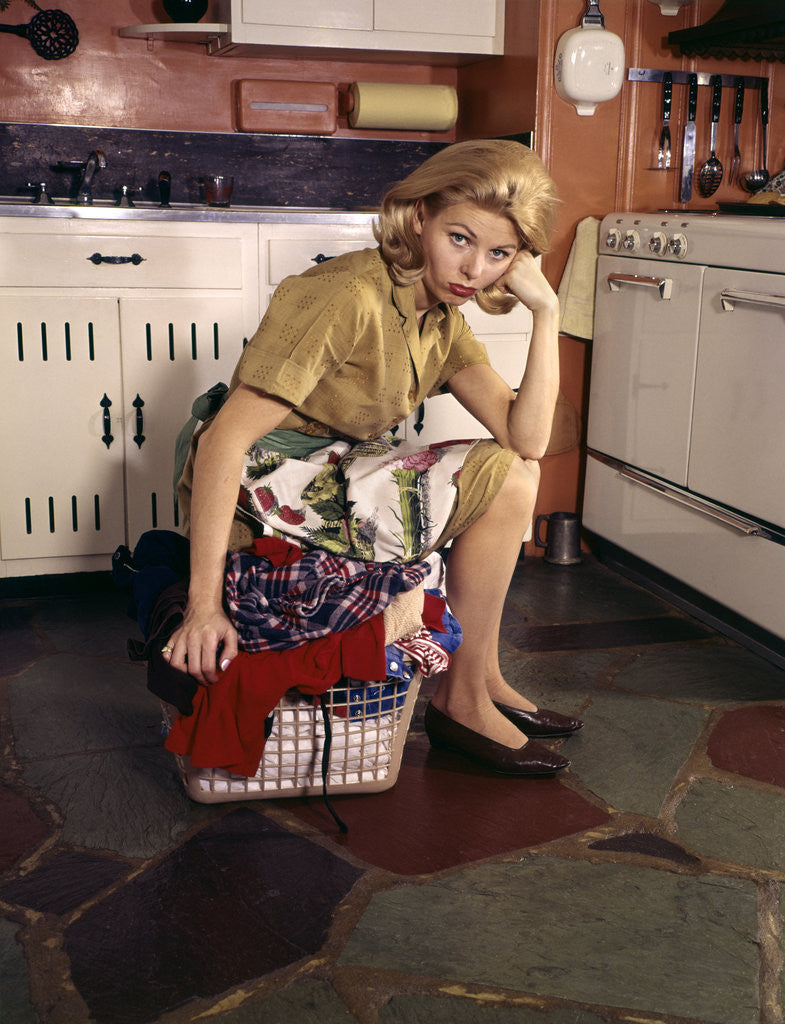 Detail of 1960s Weary Dejected Woman Housewife Homemaker Sitting On Full Laundry Basket In Kitchen by Corbis