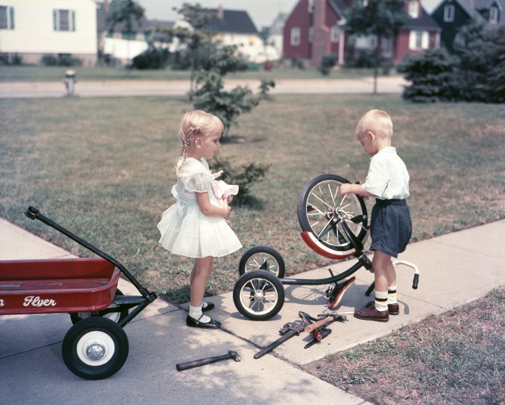 Detail of 1950s Little Girl Sister Holding Doll Watching Little Boy Brother Repair Tricycle by Corbis