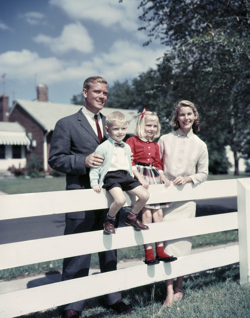 Detail of 1950s 1960s Family Portrait Mother Father Daughter Son At White Fence Of Suburban Home by Corbis