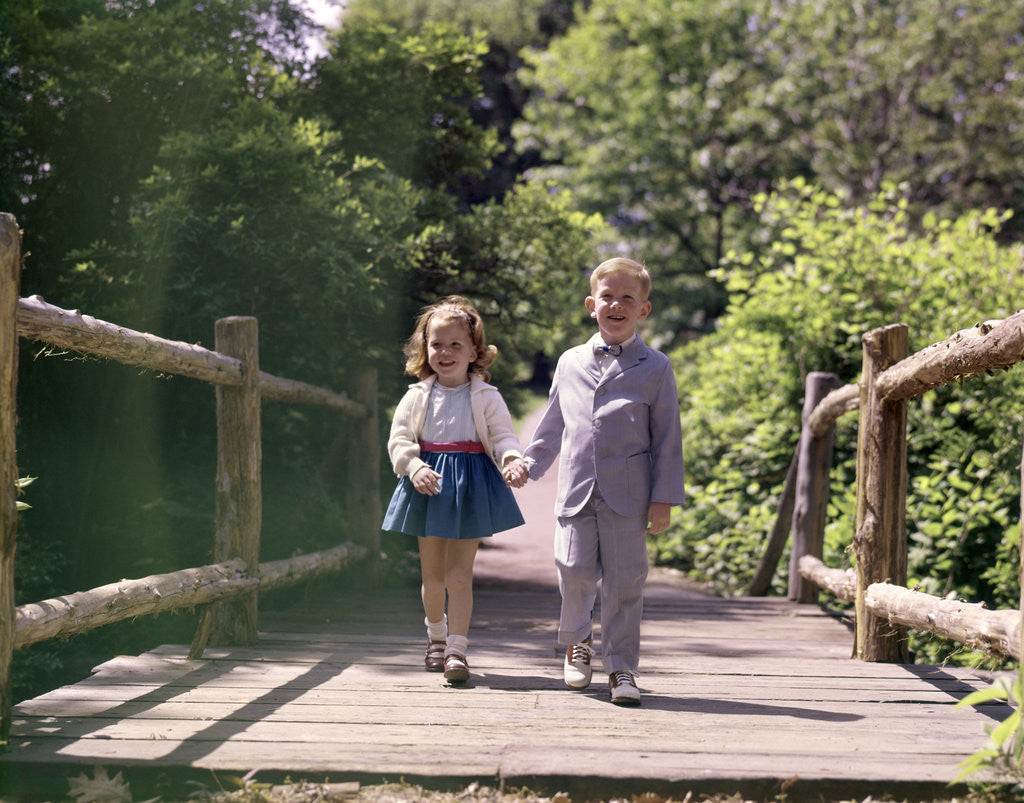 Detail of 1960s Little Boy And Girl Holding Hands And Walking Across Wooden Footbridge by Corbis