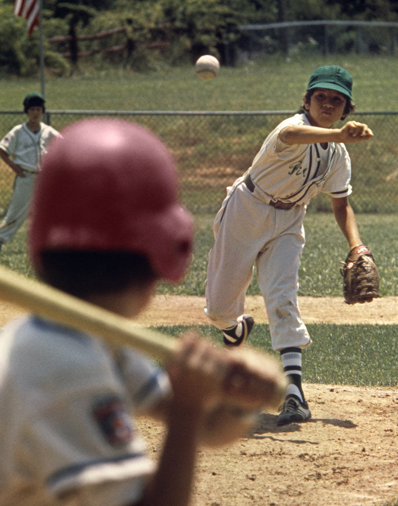 Detail of 1970s Little League Baseball Game Boy Pitcher Throwing Ball To Batter by Corbis
