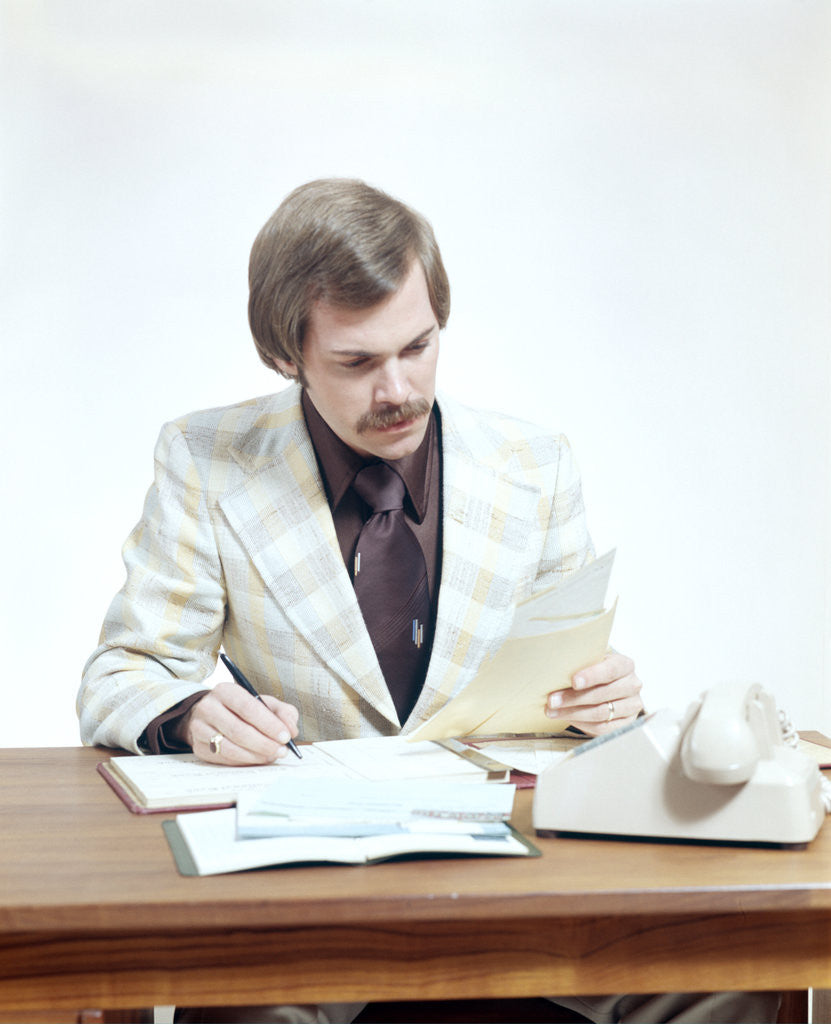 Detail of 1970s Business Man At Desk Handling Paperwork Office Telephone by Corbis