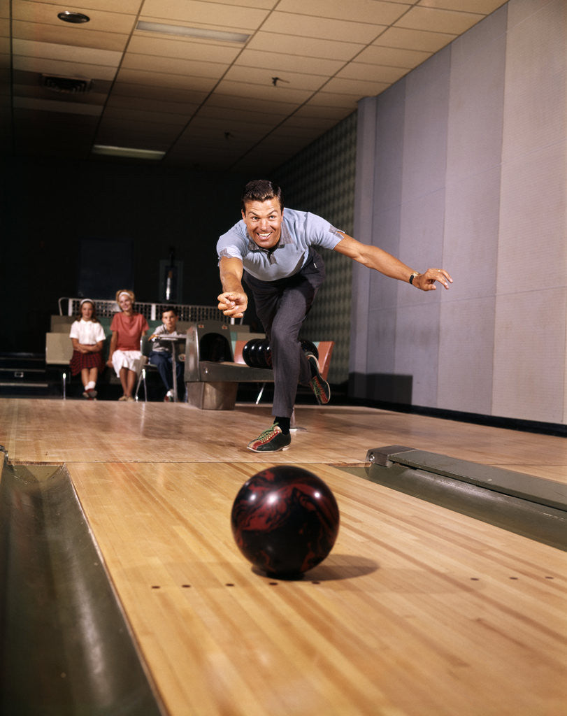 Detail of 1960s Man In Good Form Releasing Bowling Ball Down Lane Wife Woman 2 Kids Behind Him by Corbis
