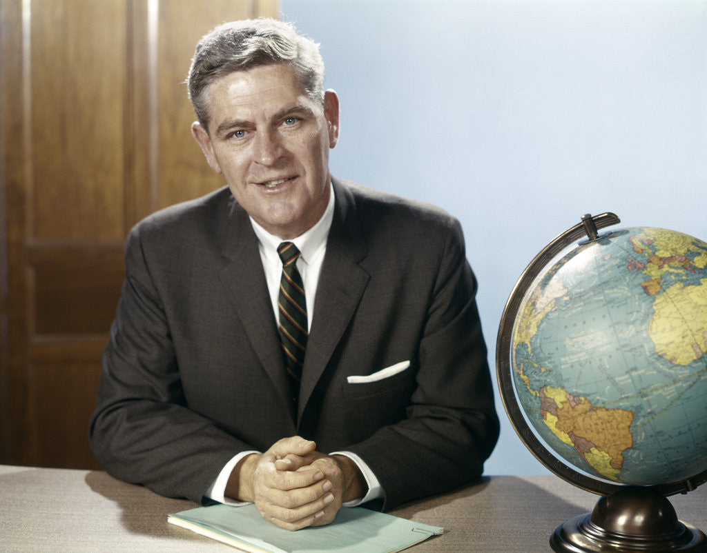 Detail of 1960s Portrait Man Businessman Sitting At Desk Next To Globe Of The Earth by Corbis
