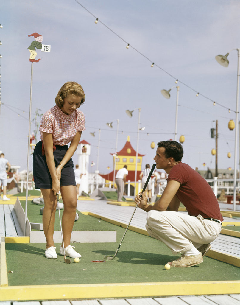 Detail of 1950s 1960s Young Couple Man Woman Play Miniature Golf Summer Amusement by Corbis