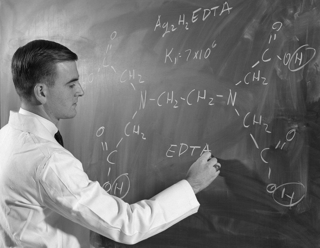 Detail of 1960s Profile Of Scientist Man In Lab Coat Writing Out Chemical Formula On Blackboard by Corbis