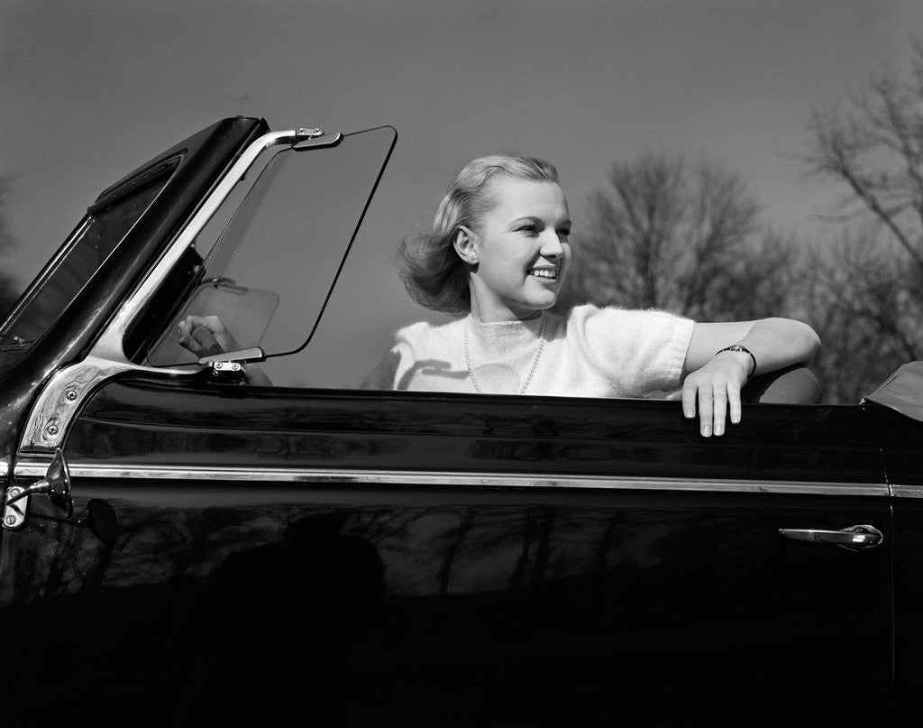 Detail of 1930s 1940s Pretty Teenage Woman Sitting In Convertible Automobile Driver Seat by Corbis