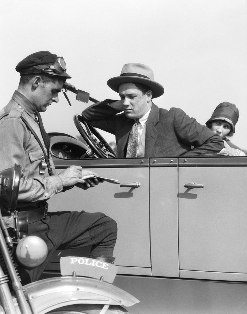 1920s Motorcycle Policeman Writing A Speeding Ticket To A Couple Sitting In Convertible Sedan by Corbis