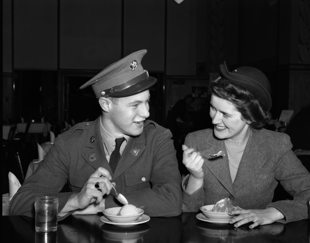Detail of 1940s Soldier In Army Uniform And Girlfriend Sitting At Soda Fountain Counter Eating Dish Of Ice Cream by Corbis