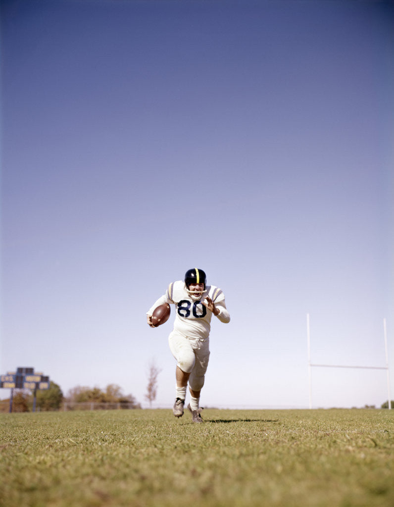 Detail of 1960s Man Football Player Carrying Ball Running Towards Camera by Corbis