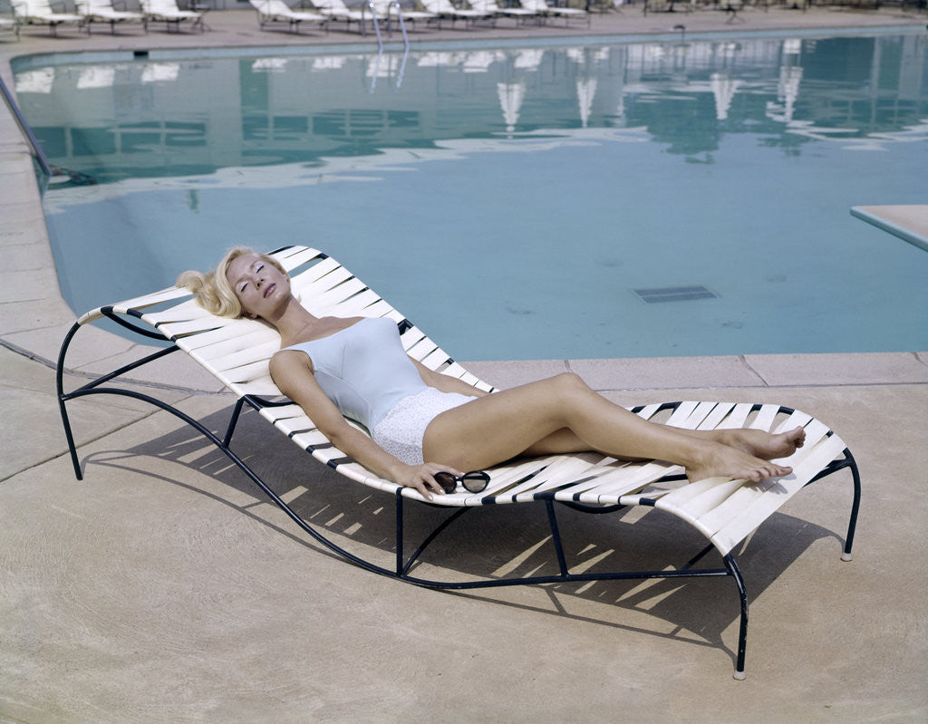 Detail of 1960s Elegant Tall Woman In Bathing Suit Reclining On A Lounge Chair By Swimming Pool by Corbis