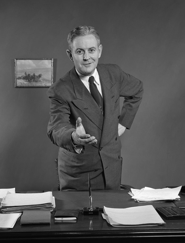 Detail of 1950s Man Businessman Salesman Reaching Across Desk To Shake Hands by Corbis