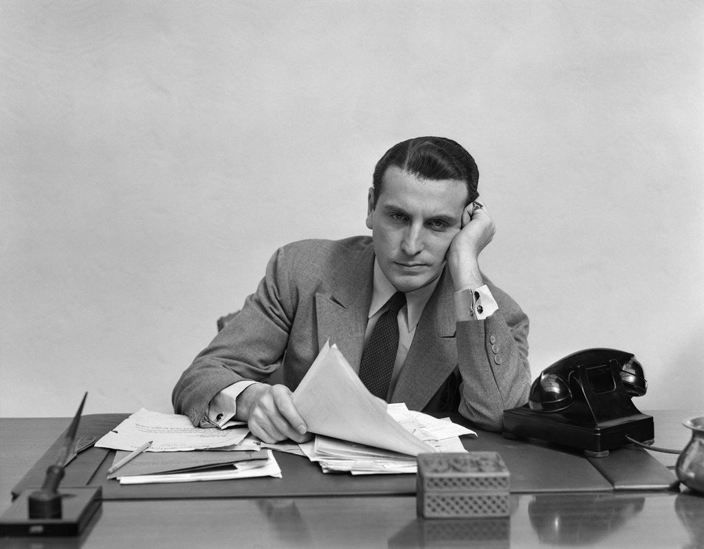 Detail of 1940s Tired Overworked Man Businessman Leaning On Elbow Looking At Camera by Corbis