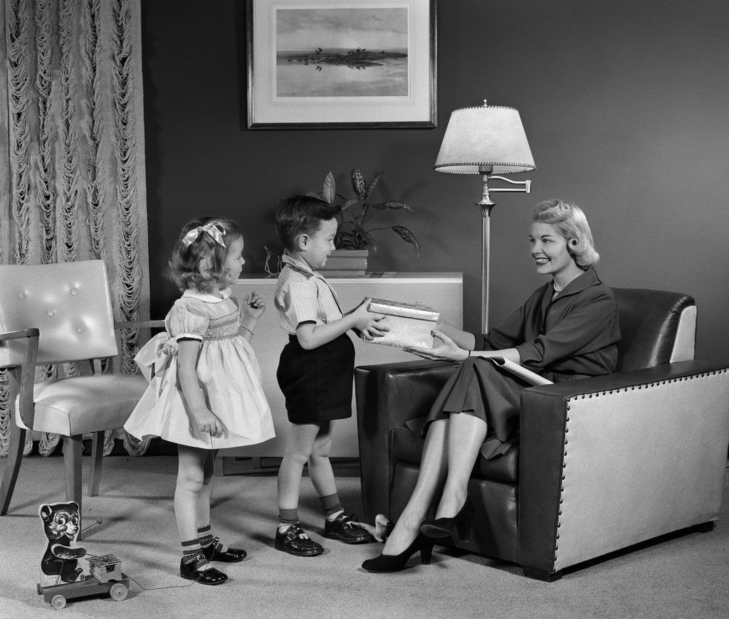 Detail of 1950s Little Boy And Girl Son And Daughter Giving Woman Mother Sitting In Living Room A Gift Present by Corbis