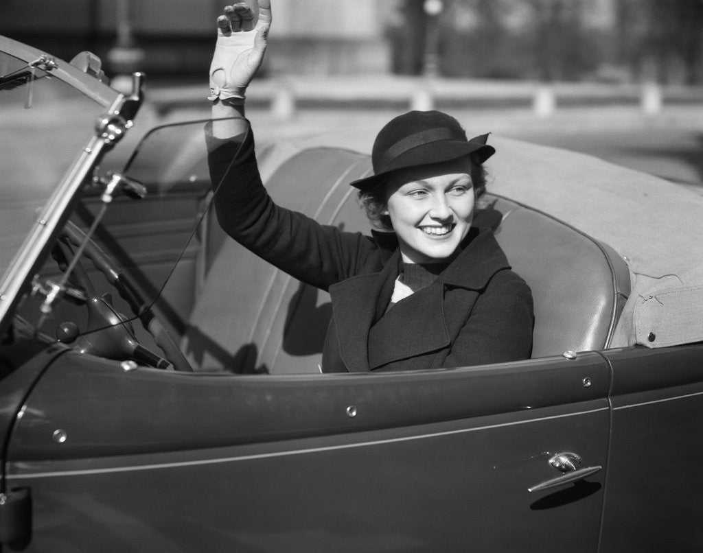 Detail of 1930s Woman Driving Convertible Roadster Automobile Waving Gloved Hand by Corbis