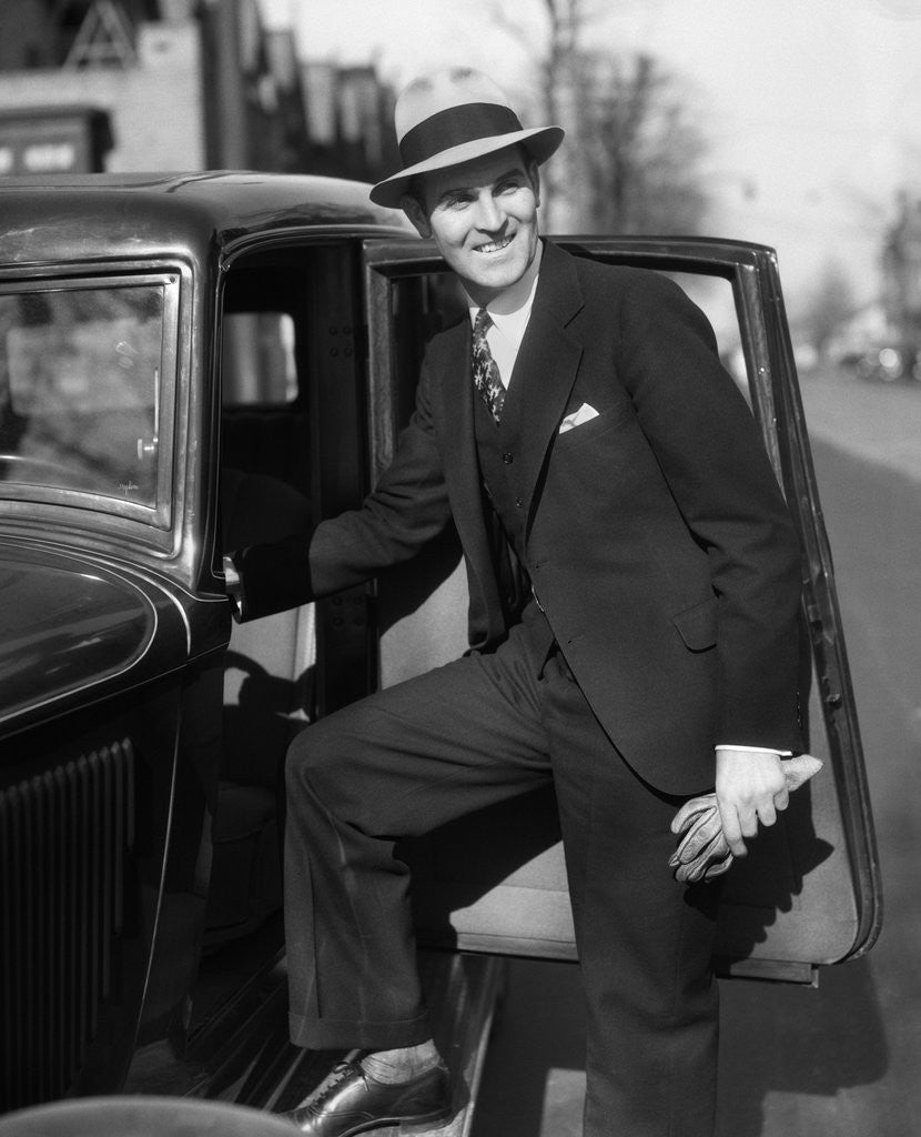 Detail of 1930s Man In Suit And Hat Holding Gloves Stepping Into Automobile Driver Seat by Corbis