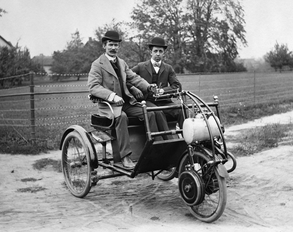 Detail of 1900s Two Men In Bowler Hats Sitting In Three Wheel Motorized Horseless Carriage by Corbis