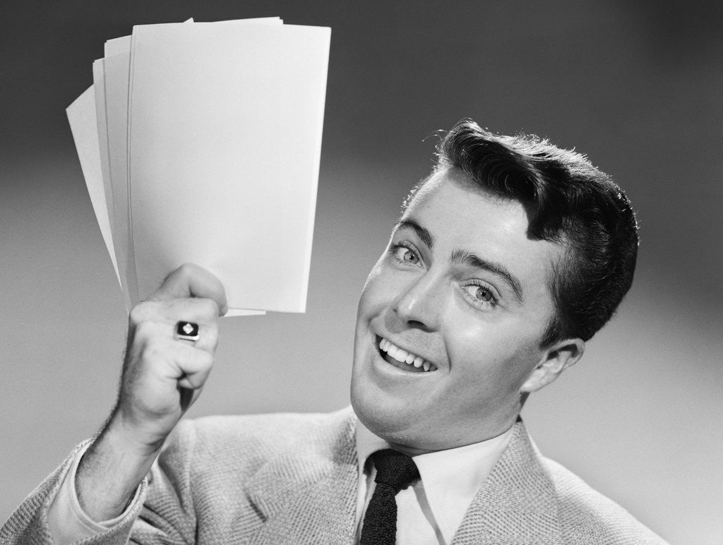 Detail of 1950s Young Businessman Holding Up Handful Of Papers by Corbis