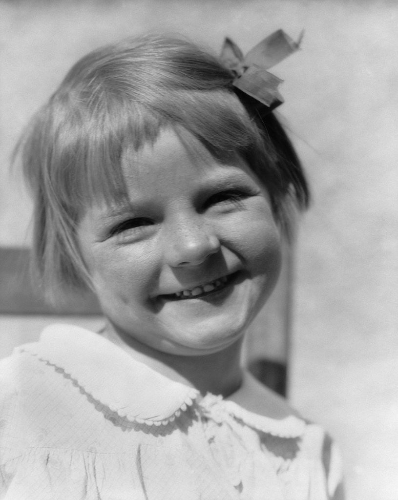 1930s Young Girl Outdoor Portrait With Freckles And Bow In Hair At Camera