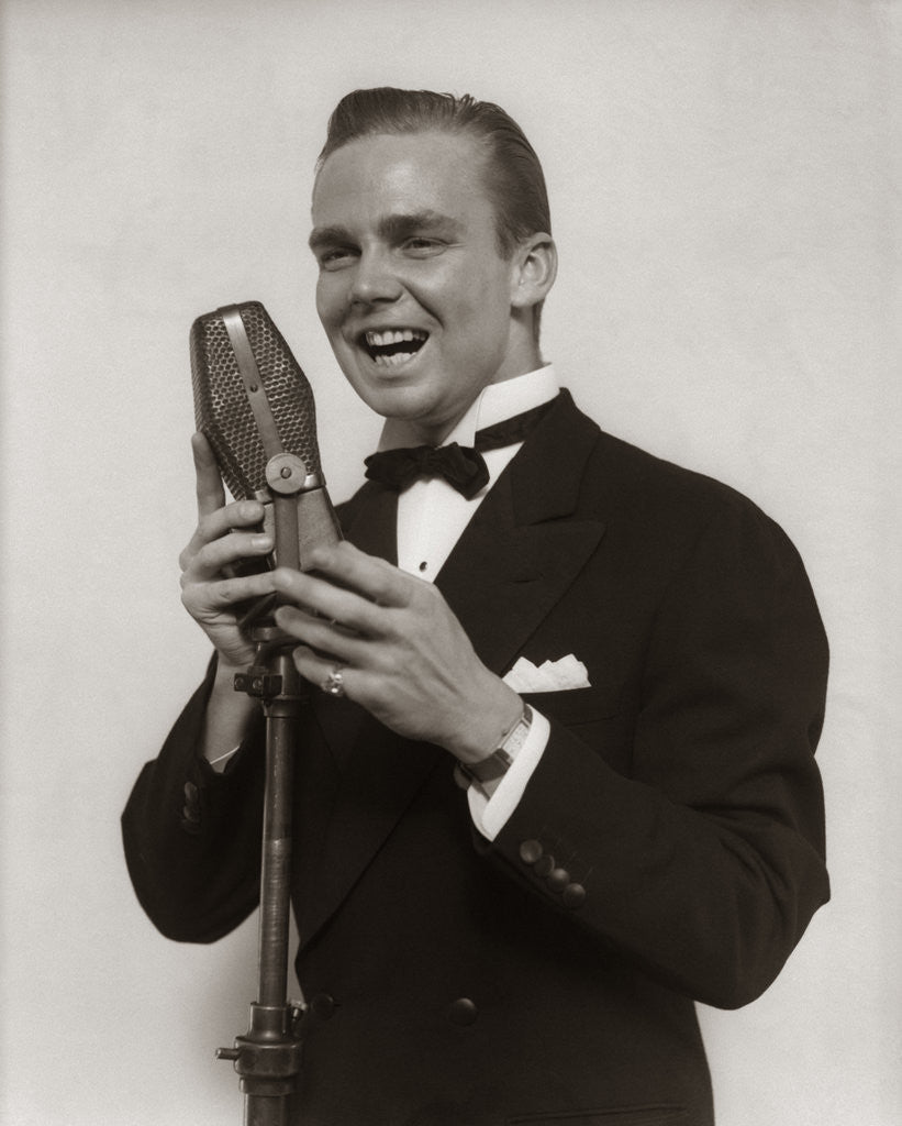 Detail of 1920s 1930s Man Radio Singer Entertainer Crooner In Tuxedo Singing Into Microphone by Corbis
