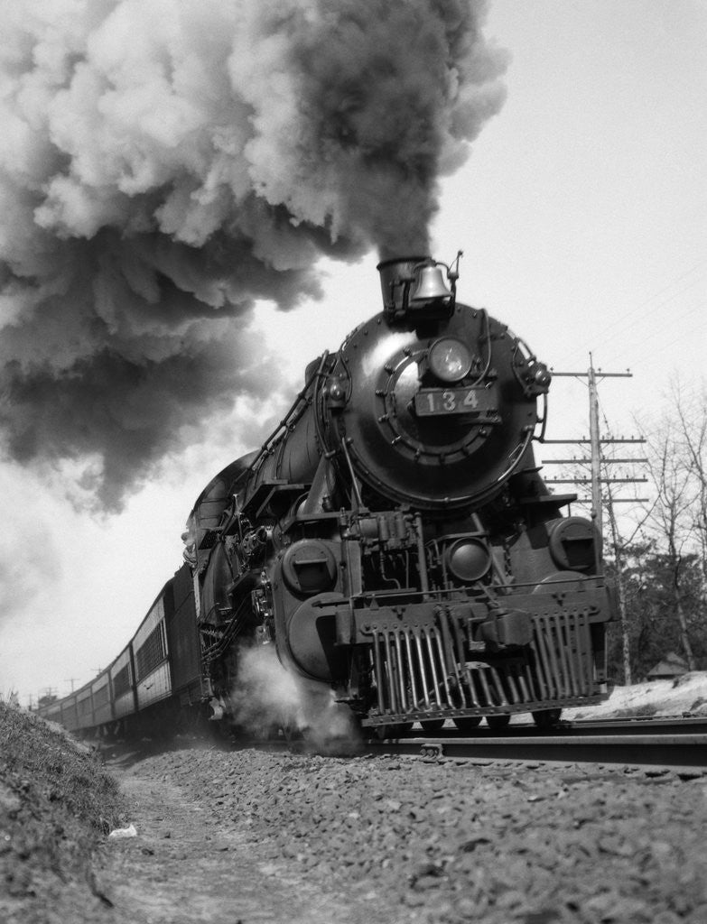 Detail of 1920s 1930s Steam Engine Pulling Passenger Train Smoke Billowing From Exhaust Stack by Corbis