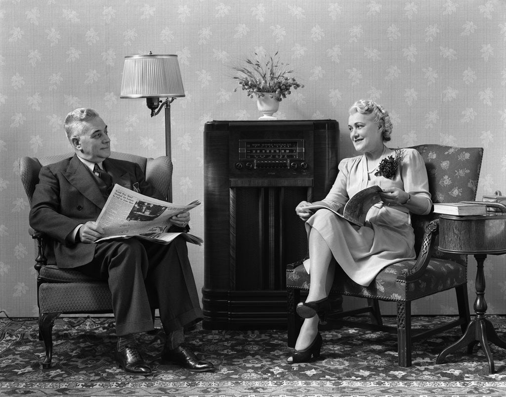 Detail of 1940s Senior Couple Sitting In Living Room Reading Newspaper And Magazine Listening To Radio by Corbis