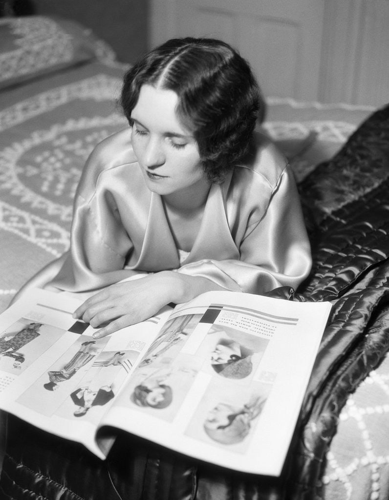 Detail of 1920s 1930s Reclining Woman With Marcel Wave Hair Style Reading A Fashion Magazine by Corbis
