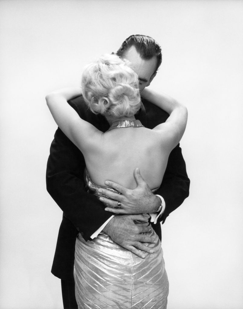 Detail of 1950s 1960s Wife In Backless Satin Gown Evening Dress And Husband Embracing And Kissing by Corbis