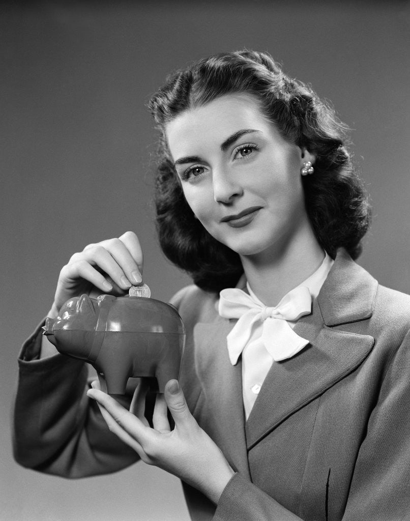 1940s Woman Putting Change Into Piggy Bank