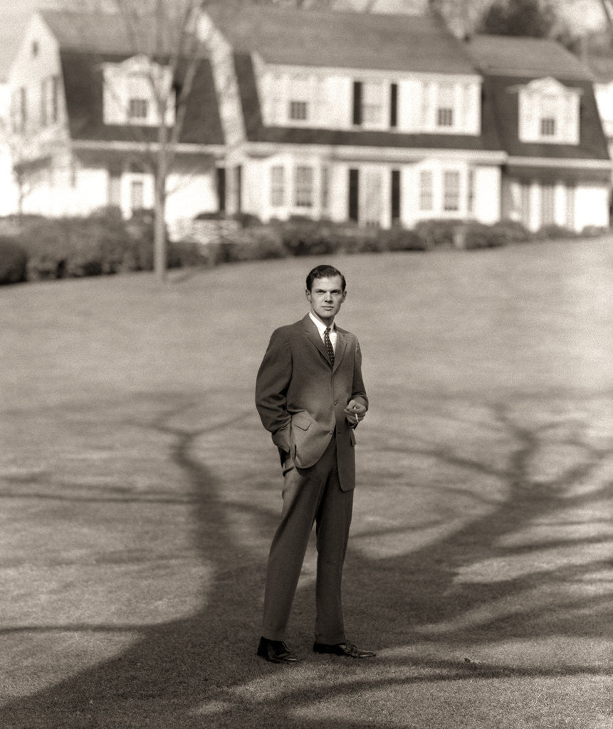 Detail of 1950s Executive In Gray Flannel Suit And Tie Standing On Suburban Home Lawn by Corbis