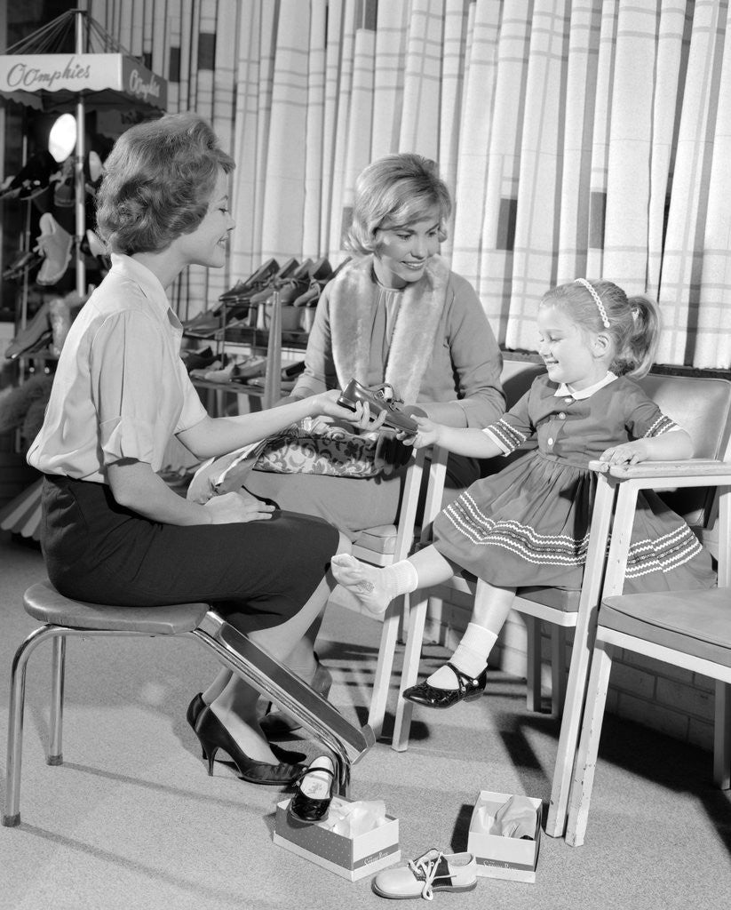 Detail of 1960s Mother Daughter Shoe Shopping Saleswoman Showing Patent Leather Shoe To Girl by Corbis
