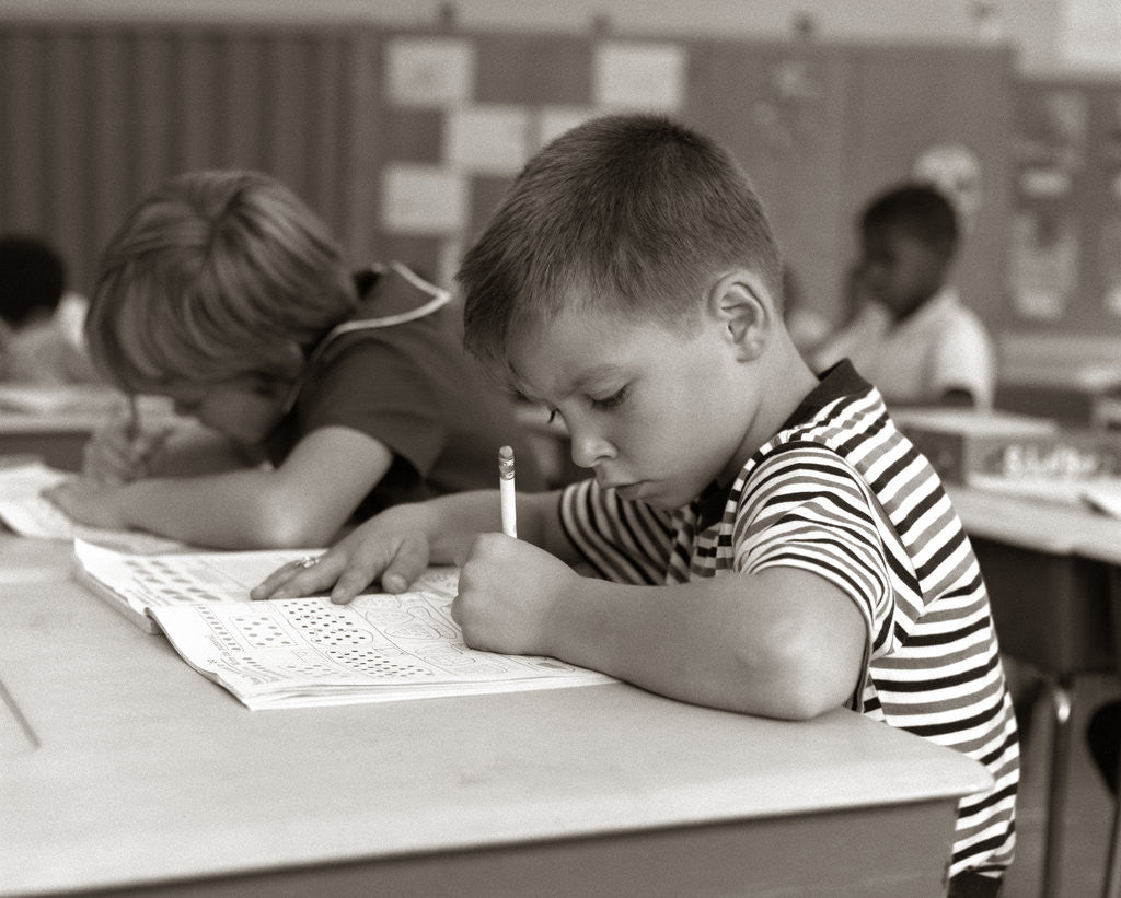 Detail of 1960s Boy Striped T-Shirt Elementary School Classroom Sitting Desk Writing Test by Corbis