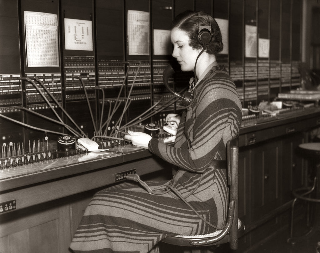 Detail of 1930s Woman Telephone Operator Sitting At Large Manual Switchboard Directing Calls by Corbis