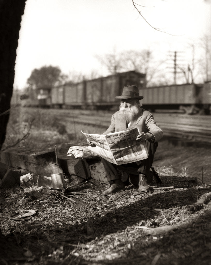 Detail of 1930s Hobo Sitting By Railroad Track Reading Newspaper During Great Depression by Corbis
