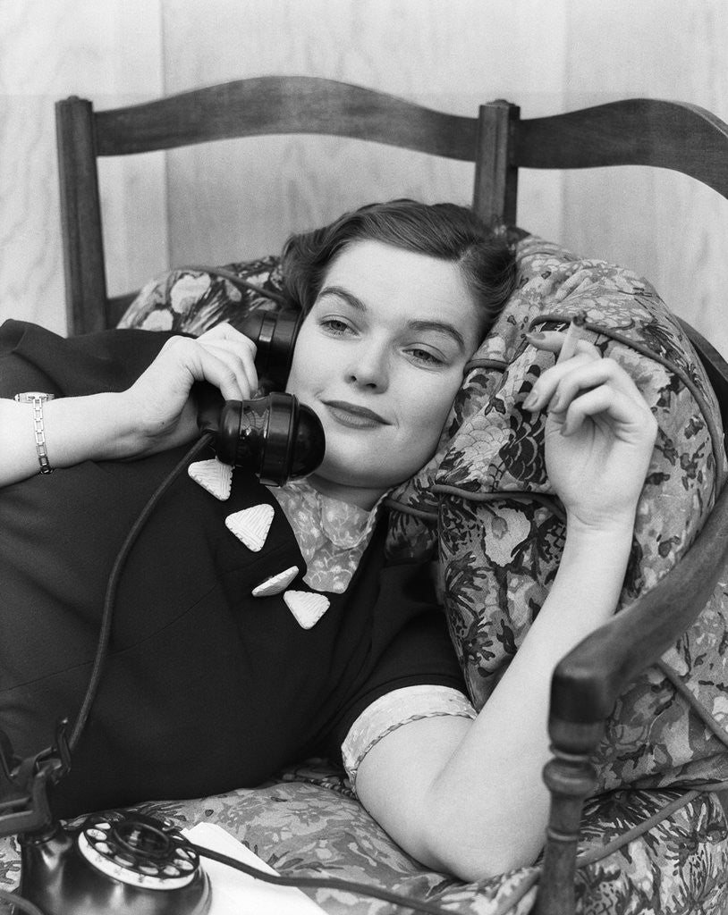 Detail of 1930s Young Brunette Woman Reclining On Pillows Cigarette In Hand Talking On Telephone by Corbis