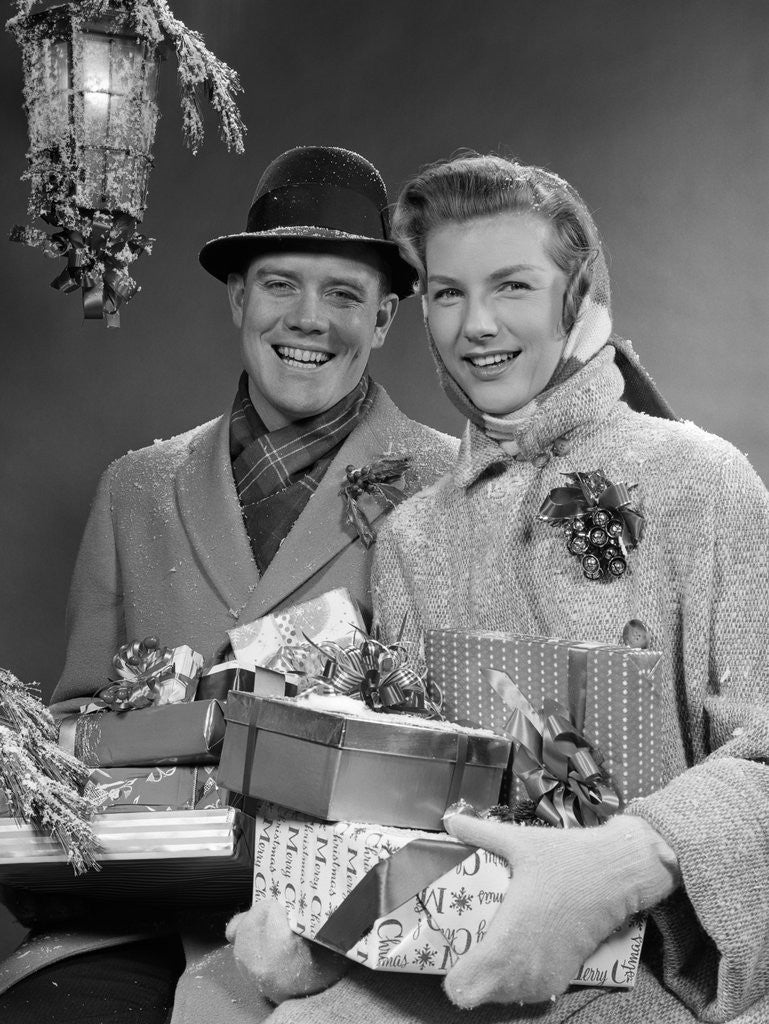 Detail of 1950s Husband And Wife Carrying Armload Of Christmas Packages Standing In Snow Under Porch Light by Corbis