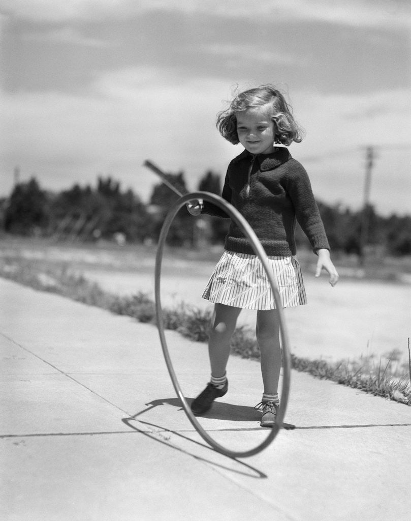 Detail of 1930s Girl Playing With Hoop And Stick On Sidewalk by Corbis
