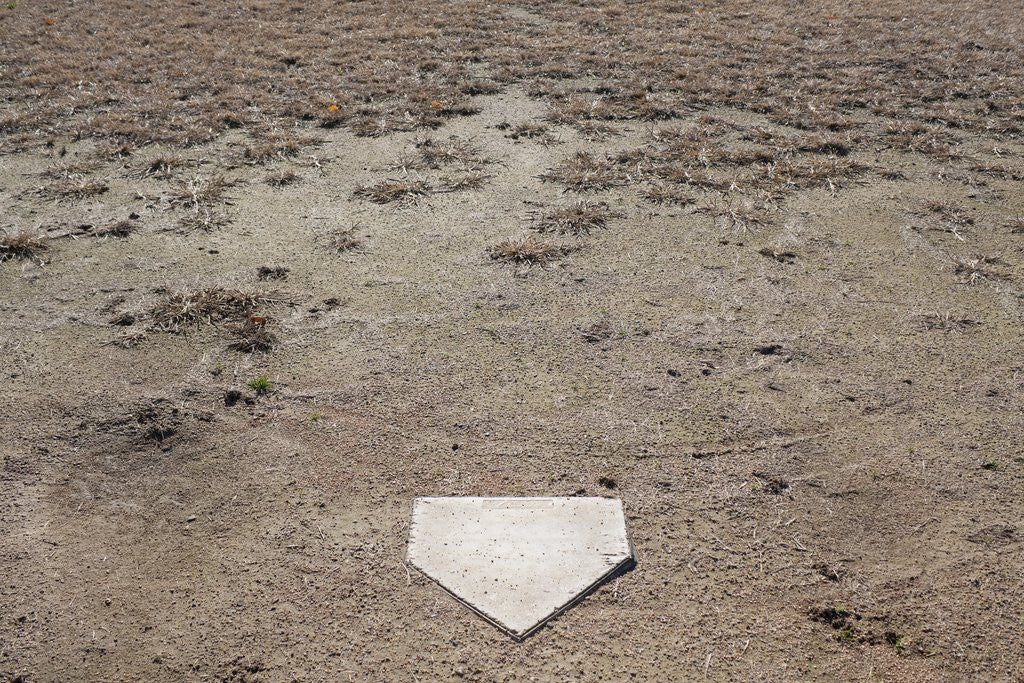 Detail of Home Plate on Field of Dirt and Dead Grass by Corbis